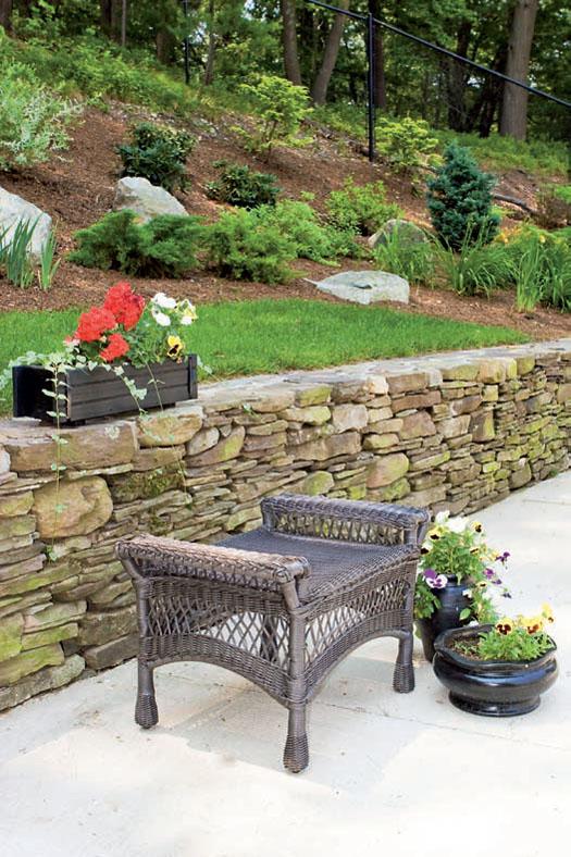 Облагородить подпорные стенки помогают различные способы кладки камня и цветочные композиции